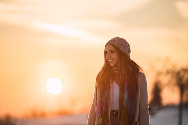 Complet du corps de l'heureuse jeune femme dans des vêtements chauds se promenant sur la neige blanche fraîche dans la campagne d'hiver au moment du coucher du soleil