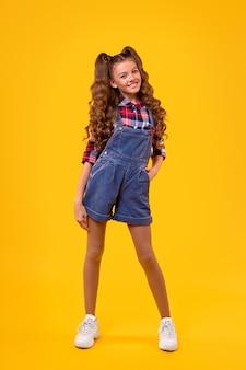Complet du corps heureux fille adolescente avec des queues de cheval habillé en chemise à carreaux et en denim avec des baskets blanches à la