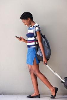 Complet du corps jeune femme africaine à pied avec sac de voyage et à l'aide de téléphone portable