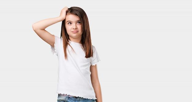 Complet du corps petite fille inquiète et dépassée, oublieux, réaliser quelque chose