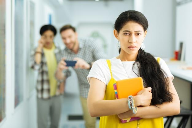 Comportement idiot. triste malheureuse jeune fille victime d'intimidation à l'université et en appuyant sur ses notes sur la poitrine pendant que deux hommes la prennent en photo