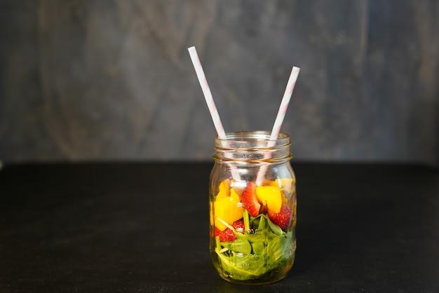 Composants d'un smoothie aux vitamines green reach en bonne santé avec des pousses d'épinards, de mangue, de lait d'amande et de fraises