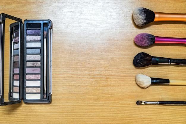 Composez la mode de beauté de produit de brosse cosmétique sur le fond en bois