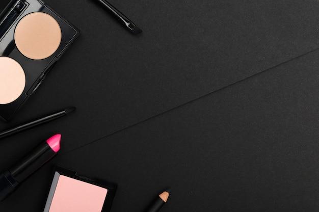 Composez les produits sur fond noir. poudre, palettes de fard à joues, rouge à lèvres, eye-liner, pinceaux d'en haut.
