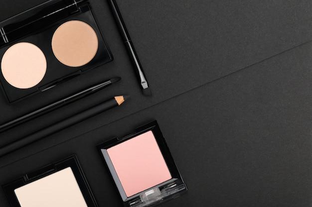 Composez les produits sur fond noir. poudre, palettes de fard à joues, rouge à lèvres, eye-liner et pinceaux