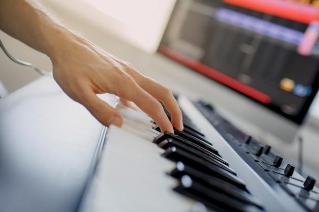 Compositeur mains sur les touches du piano en studio d'enregistrement. technologie de production musicale, l'homme travaille sur le pianino et le clavier de l'ordinateur sur le bureau. gros plan concept.