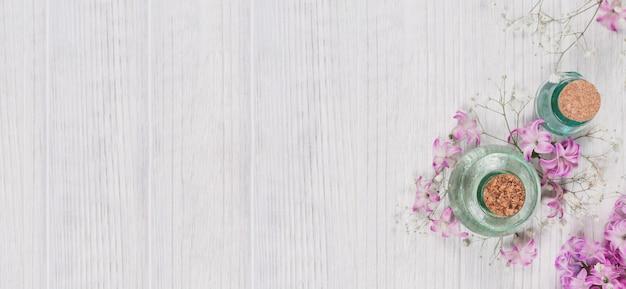 Composition abstraite de fleurs de jacinthes violettes fraîches et de bouteilles de cosmétique biologique avec de l'huile essentielle pour l'aromathérapie, la médecine alternative et la parfumerie, surface en bois rustique blanche.
