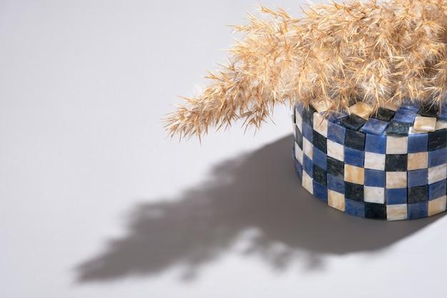 Composition abstraite de l'herbe de la pampa sur un podium de carrés minéraux avec de l'ombre.
