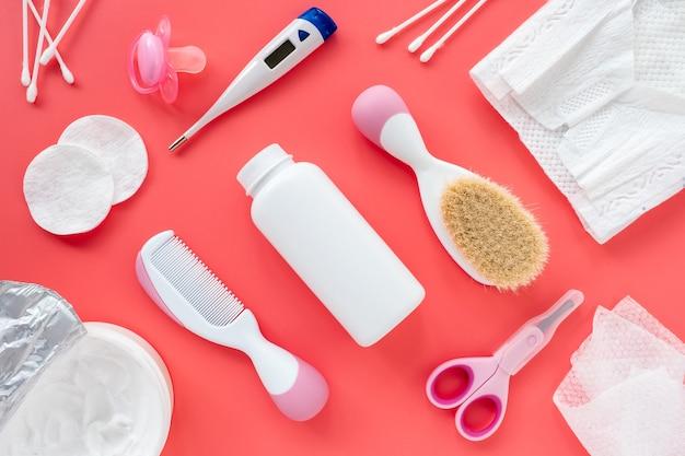 Composition avec accessoires pour bébé et cosmétiques pour la garde d'enfants sur fond rose, plat, vue de dessus, mise en page. contexte tendance, hygiène des filles nouveau-nées.