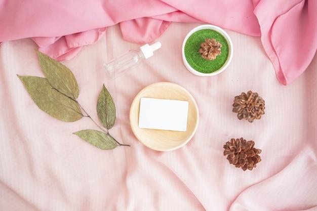 La composition affiche le produit. bâtons en bois et cartes de visite décorés de tissu, de bouteilles cosmétiques, de feuilles séchées et de fleurs de pin. composition minimaliste mettant en vedette des produits