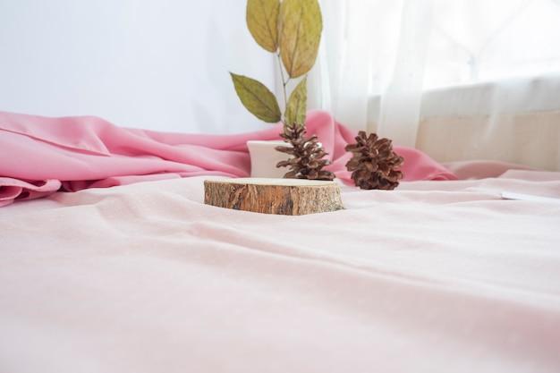 La composition affiche le produit. bâtons en bois pour exposer des produits décorés de tissu, de feuilles séchées et de fleurs de pin. composition minimaliste mettant en vedette des produits