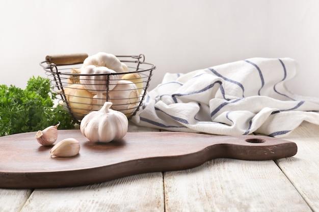 Composition avec de l'ail frais sur une table en bois clair