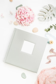Composition avec album photo de mariage ou de famille, bouquet de fleurs d'hortensia, branche d'eucalyptus, couverture rose pastel, décor de feuille de monstera sur surface blanche