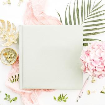 Composition avec album photo de mariage ou de famille, bouquet de fleurs d'hortensia, feuille de palmier tropical, couverture rose pastel, plaque de monstera or sur surface blanche