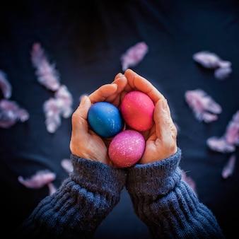 Composition alternative de pâques dans un style sombre avec des oeufs de couleur bleu et rose classique, plume et mains de femme senior sur surface noire, concept de vacances de printemps