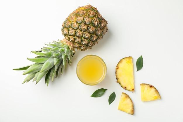 Composition avec ananas, tranches et verre de jus sur fond blanc, espace pour le texte