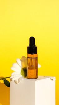 Composition d'aromathérapie sur mur jaune. huile essentielle de camomille dans un flacon en verre avec de la camomille.
