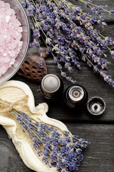 Composition aromatique de lavande, d'herbes, de cosmétiques et de sel sur un dessus de table sombre