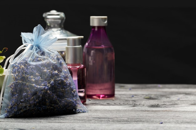Composition aromatique de lavande, d'herbes, de cosmétiques et de sel sur un plateau sombre