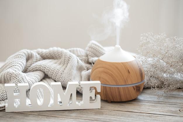 Composition d'arôme avec diffuseur d'huile d'arôme moderne sur une surface en bois avec un élément tricoté et une maison de mot décoratif en bois.