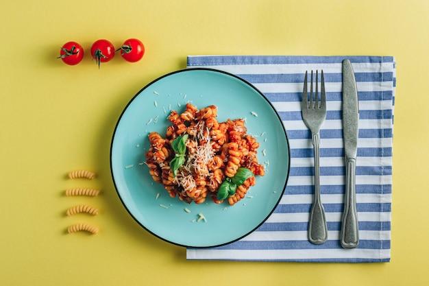 Composition avec assiette de pâtes tomate basilic serviette et couverts sur fond jaune plat créatif lay