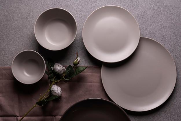 Une composition d'assiettes et de tasses grises, avec une fleur rose. appartement romantique sombre posé sur un fond gris.