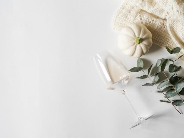 Composition d'automne blanc plat poser - citrouilles, eucalyptus, plaid, vin blanc en verre.