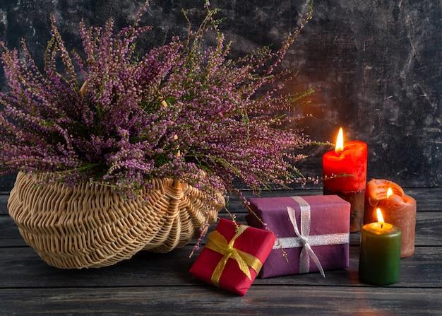 Composition d'automne de bruyère dans un panier en osier et cadeaux nature morte