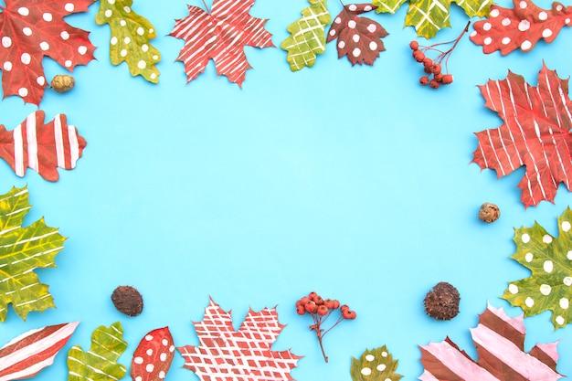 Composition d'automne. cadre en érable créatif à feuilles séchées, chêne peint à rayures, pois sur fond bleu.