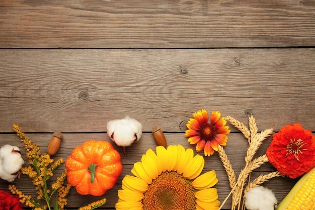 Composition d'automne. cadre fait de fleurs fraîches sur fond de bois gris. mise à plat, vue de dessus, espace de copie. jour de thanksgiving