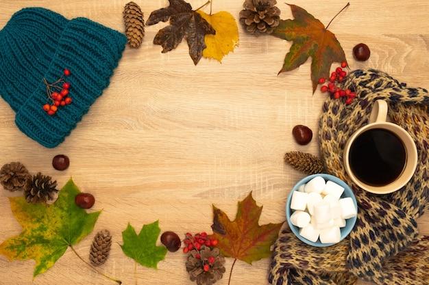 Composition d'automne avec chapeau, feuilles et guimauves. tourné d'en haut sur un fond en bois. place pour votre texte.