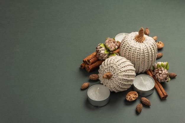 Composition d'automne avec citrouilles au crochet, bougies, épices et décor traditionnel. un fond gris foncé à la mode, place pour le texte