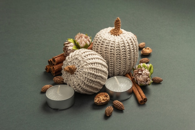 Composition d'automne avec citrouilles au crochet, bougies, épices et décor traditionnel. un fond gris foncé tendance, gros plan