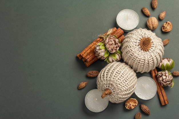 Composition d'automne avec citrouilles au crochet, bougies, épices et décor traditionnel. un fond gris foncé tendance, vue de dessus