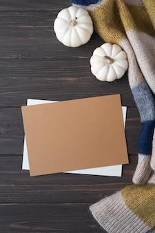 Composition d'automne confortable avec papier brun vierge, citrouille et couverture tricotée en laine sur table en bois.