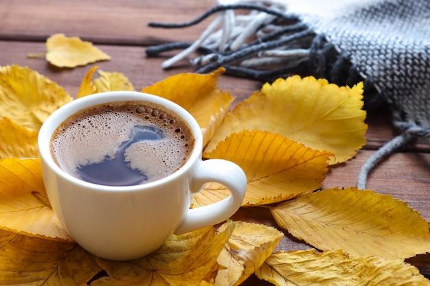 Composition d'automne confortable avec une tasse de café à carreaux chauds et des feuilles d'automne jaunes mise au point sélective