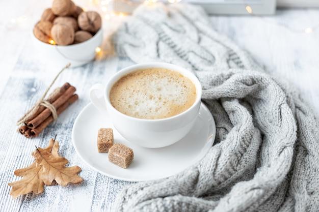 Composition d'automne confortable avec une tasse de café, sucre brun, écharpe tricotée, guirlande