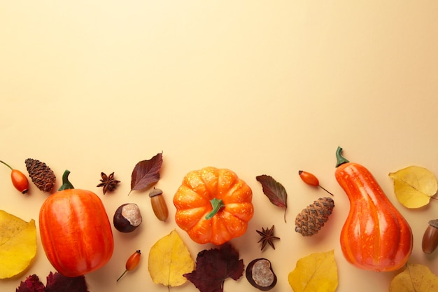 Composition d'automne créative. citrouilles oranges avec des feuilles sur fond beige. vue de dessus