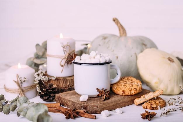 Composition d'automne avec du cacao avec des biscuits aux guimauves citrouille et bougies