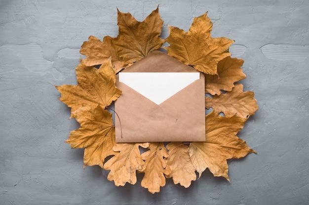 Composition d'automne. enveloppe artisanale. carte vierge avec des feuilles d'érable automne. lay plat, vue de dessus, espace de copie.