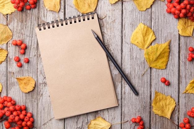 Composition d'automne avec espace de travail avec cahier vierge, crayon et belles feuilles d'érable rouge. vue de dessus, mise à plat, tonification vintage. concept de détente automne