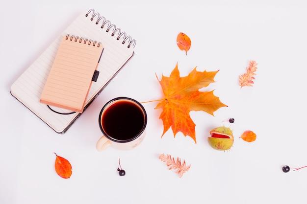 Composition d'automne faite de feuilles d'érable multicolores sèches d'automne, de baies, de châtaigne, de tasse de café ou de thé, bloc-notes sur fond blanc. automne, concept d'automne. mise à plat, vue de dessus, espace de copie