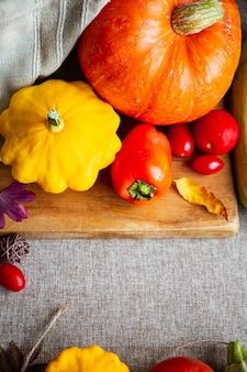 Composition d'automne festive de citrouilles, feuilles, tomates et courges sur fond beige. concept de thanksgiving ou halloween