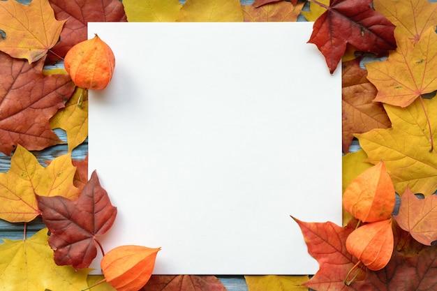 Composition d'automne de feuilles d'érable et de papier blanc carré. lay plat, vue de dessus