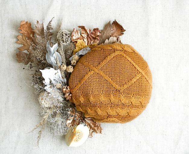 Composition d'automne avec des fleurs séchées et élément tricoté dans l'espace de copie central.
