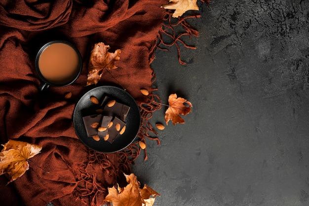 Composition d'automne. foulard marron, café au lait, chocolat noir aux amandes et feuilles d'érable d'automne. mise à plat. vue de dessus. photo de haute qualité