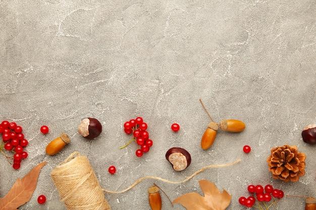 Composition d'automne sur gris, cadre en pommes de pin, glands et châtaignes. mise à plat, vue de dessus.