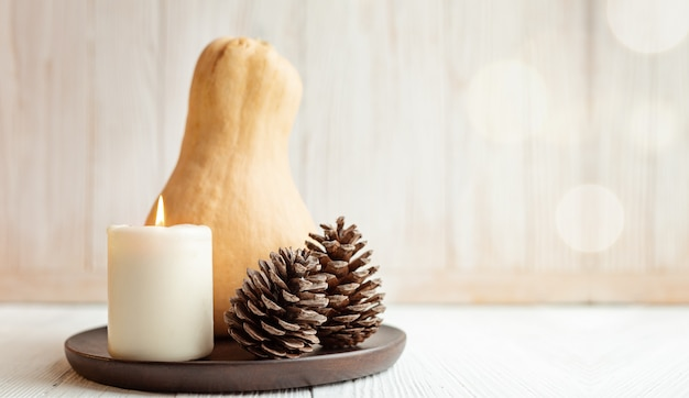 Composition d'automne ou d'hiver avec citrouille, bougie et pommes de pin style scandinave hygge flou