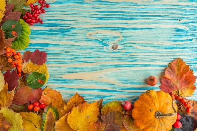 La composition d'automne laisse des baies de citrouille sur fond bleu concept d'action de grâces à plat l'espace de copie