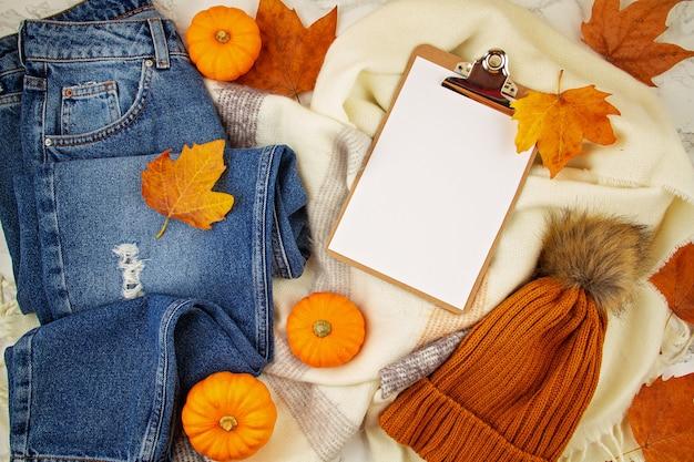 Composition d'automne à plat avec des feuilles d'automne, des citrouilles, un jean et une écharpe en laine chaude et un chapeau